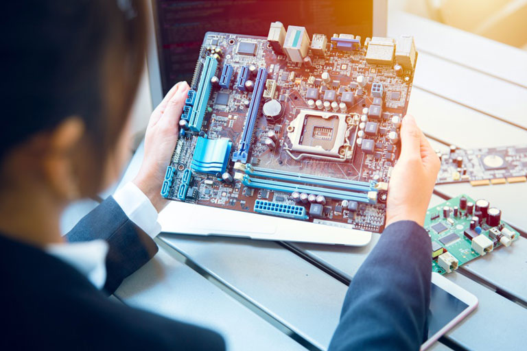 Young woman computer hardware engineer holding / looking at a motherboard