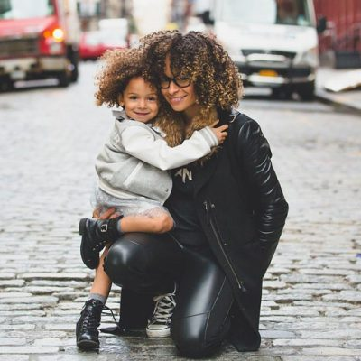 Stylish mixed-race woman hugging her daughter. with street in the background