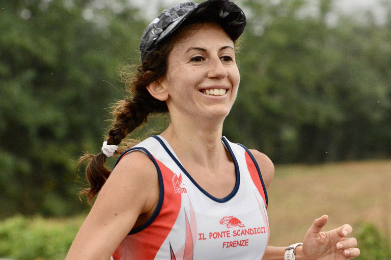 Woman with hair in braid and wearing a cap running a foot race