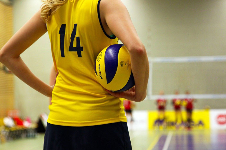 Young woman volleyball player with ball under her arm, waiting to serve