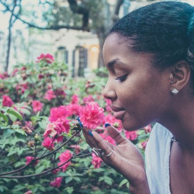 Young African-American woman peacefully smelling flowers