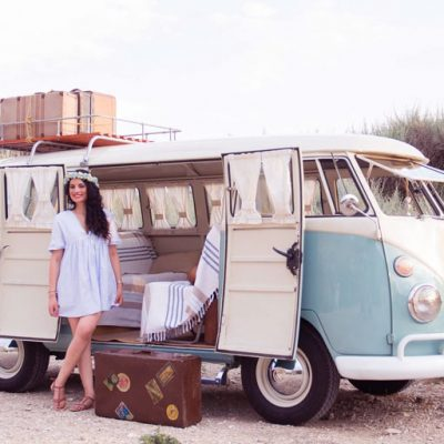 Young smiling woman with long hair stands outside of VW van home