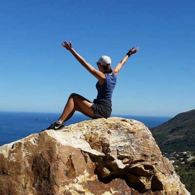 "Woman sitting on large boulder at high altitude with her arms raised in a ""V"""