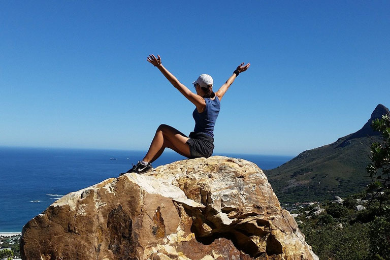 Woman sitting on top of large boulder at high altitude with her arms raised in a V